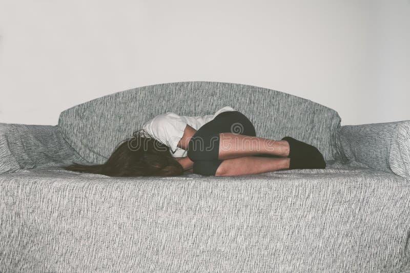 作为年轻感觉被虐待的哭泣的妇女沮丧和凄惨,当单独坐在她的屋子里时的她 免版税库存图片