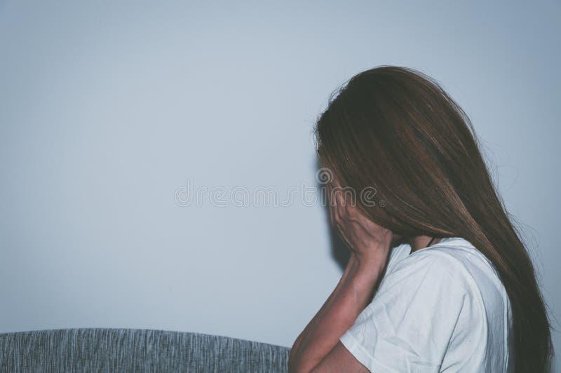 作为年轻感觉被虐待的哭泣的妇女沮丧和凄惨,当单独坐在她的屋子里时的她 免版税图库摄影