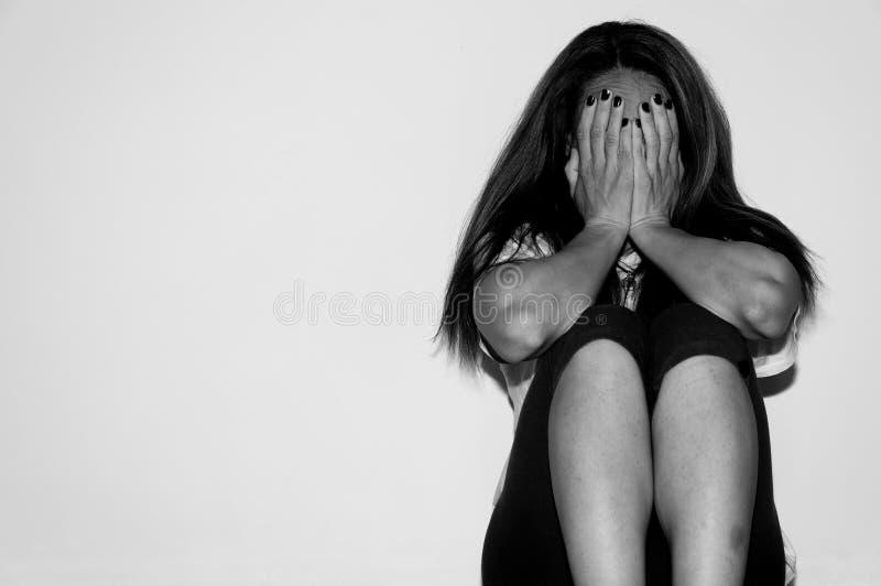 作为年轻感觉被虐待的哭泣的妇女沮丧和凄惨,当单独坐在她的屋子里时的她 免版税库存照片
