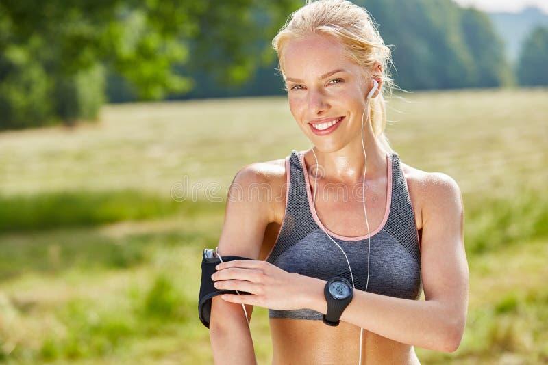 作为慢跑者的妇女与wearables 库存照片