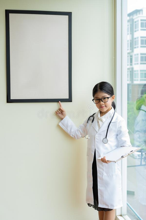 作为护士打扮的小女孩举行报告 库存照片
