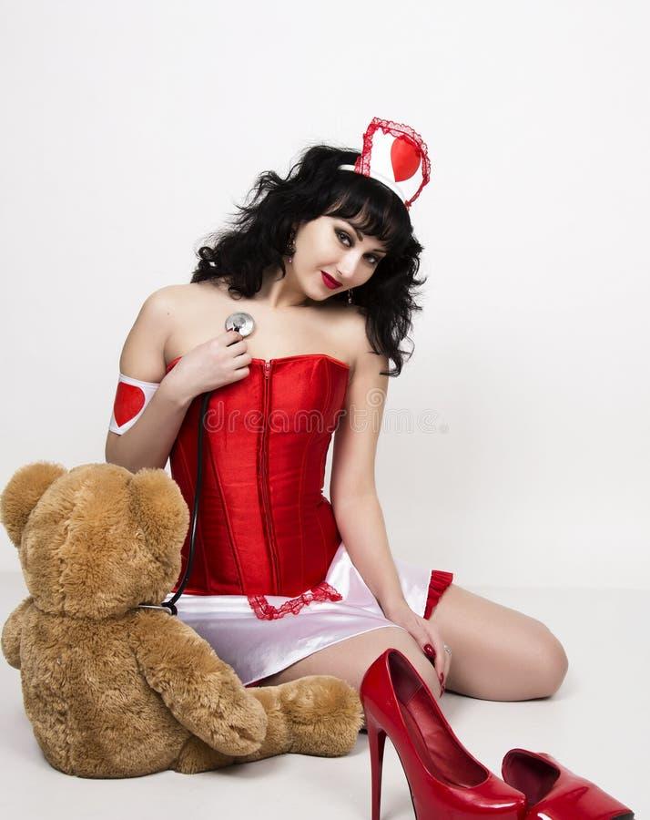 作为护士打扮的年轻美丽的妇女,医疗狂欢节服装,她拿着听诊器和坐一个地板与 库存照片