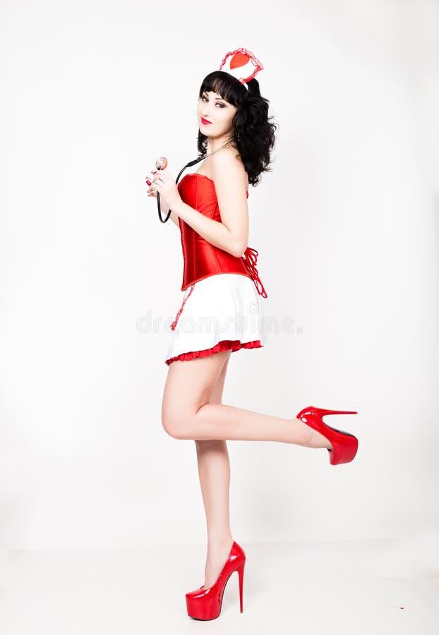 作为护士打扮的年轻美丽的妇女,医疗狂欢节服装,拿着听诊器的她 库存照片