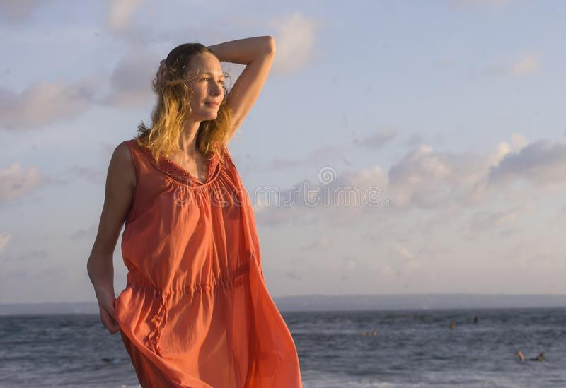 作为摆在海滩的年轻愉快的美丽和迷人的白肤金发的妇女佩带时髦的新鲜礼服微笑的快乐的感觉和fr 免版税图库摄影
