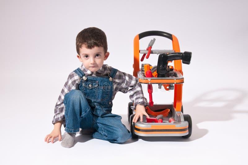 作为有推车工具的一名工作者打扮的孩子 免版税库存照片