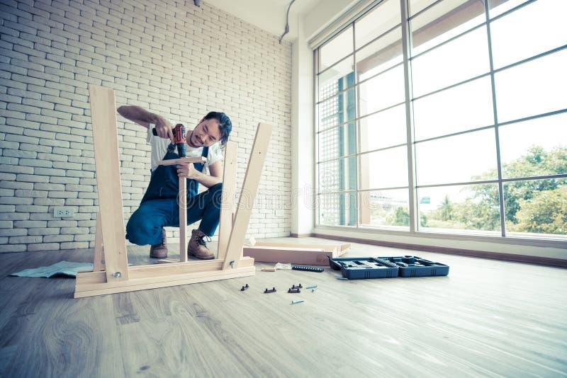 作为杂物工,与equipm的聚集的木桌的年轻人工作 库存图片