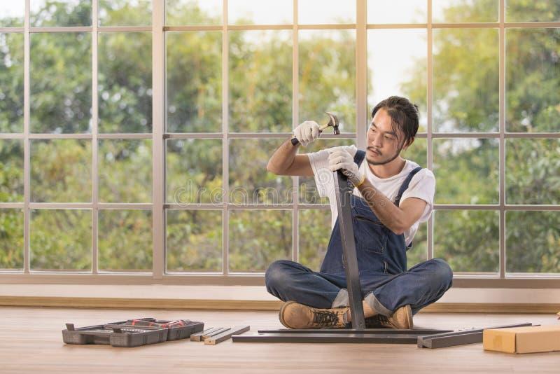 作为杂物工,与equipm的聚集的木桌的年轻人工作 免版税库存照片
