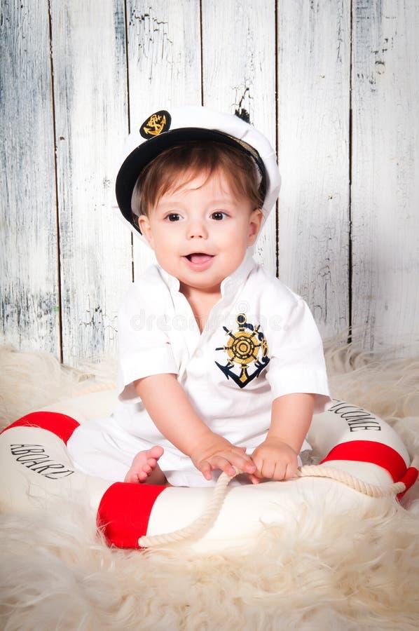 作为海军盖帽的船长打扮的滑稽的微笑的小男孩 海洋装饰,救生带 免版税库存照片