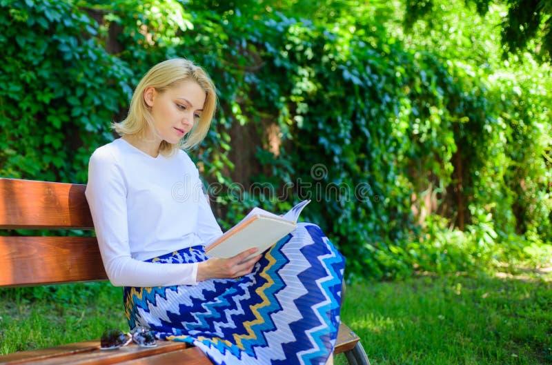 作为爱好的读书文学 书是她的激情 女孩坐放松与书,绿色自然背景的长凳 妇女 免版税库存照片
