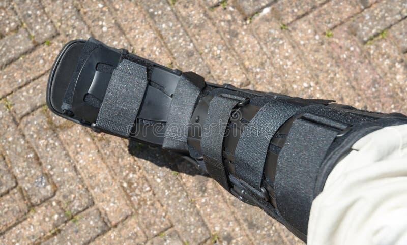 作为矫形设备的黑人步行者在脚腕手术以后 库存照片