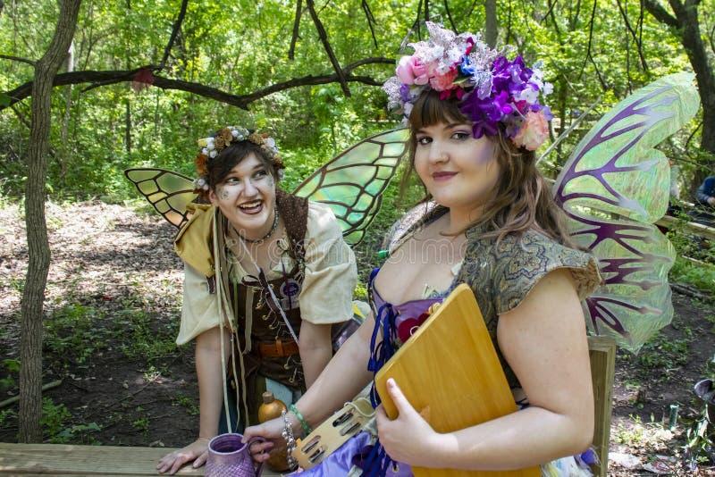 作为神仙打扮的两个女孩在森林-一看mischivously照相机的和其他嘲笑她俄克拉何马Renai 库存图片