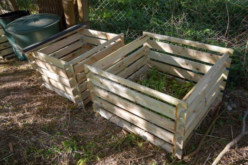 作为简单的木筒仓的混合肥料箱在庭院里 库存照片
