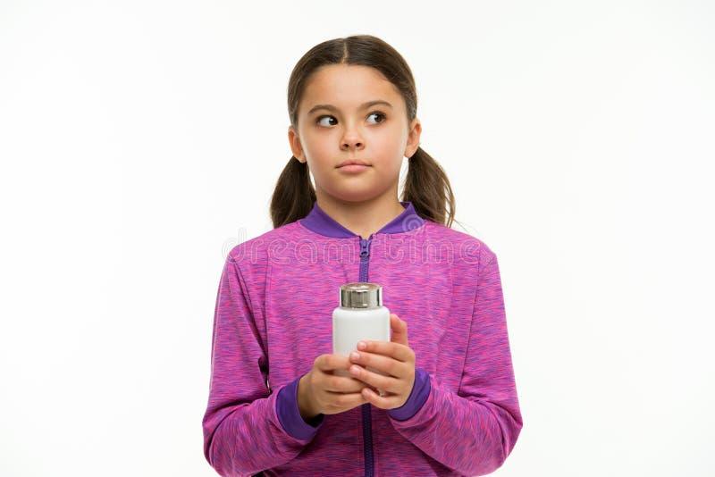 作为维生素补充 滋补饮食帮助身体是健康的 女孩长发机警的举行塑料瓶隔绝了白色 免版税库存照片