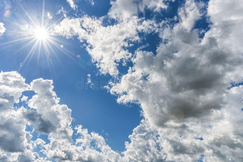 作为背景的多云蓝天 直接阳光,在云彩上的太阳 免版税图库摄影