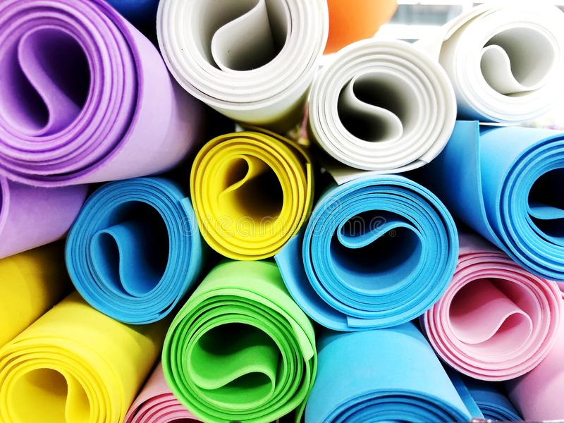 作为背景的许多五颜六色的瑜伽席子 反对白色的滚动的瑜伽锻炼席子 免版税图库摄影