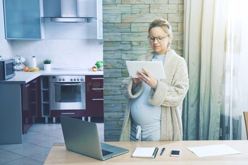 作为自由职业者的孕妇工作有片剂的 库存图片