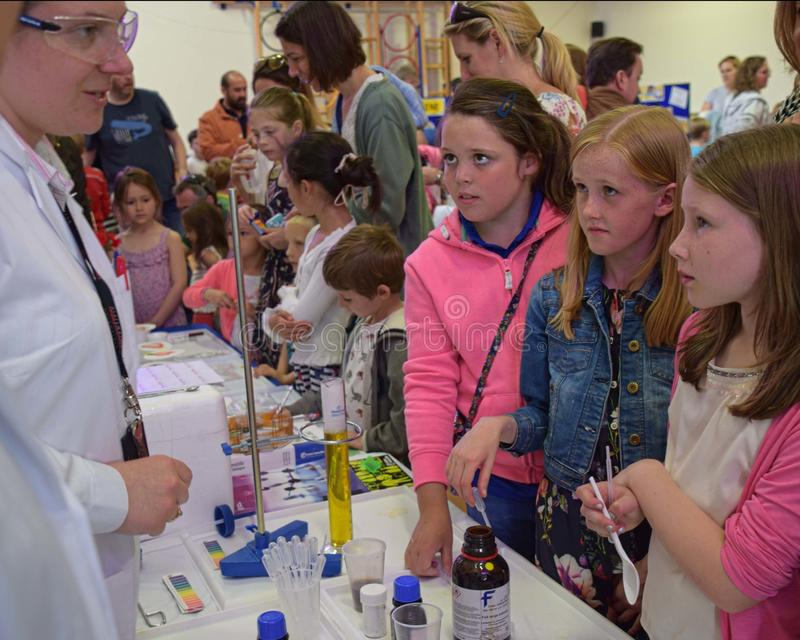 作为英国词根一部分,实验室化学家需要一天在实验室外面教关于化学,科学,技术,引擎的孩子 库存图片