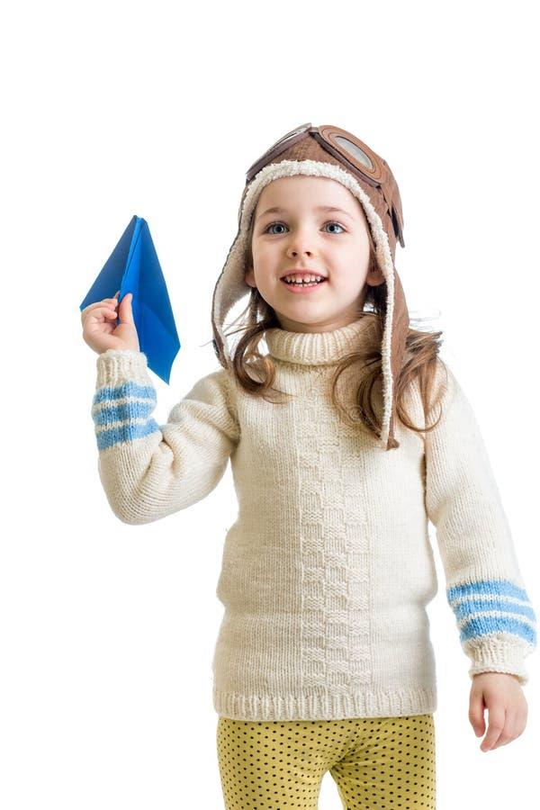 作为飞行员打扮的儿童女孩使用与纸飞机isol 库存照片