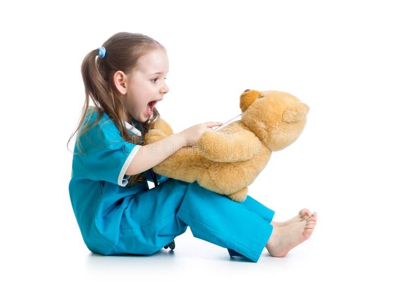 作为医生打扮的可爱的孩子使用与玩具熊 库存照片