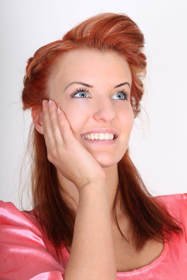 作头发的愉快的红色妇女 免版税库存图片