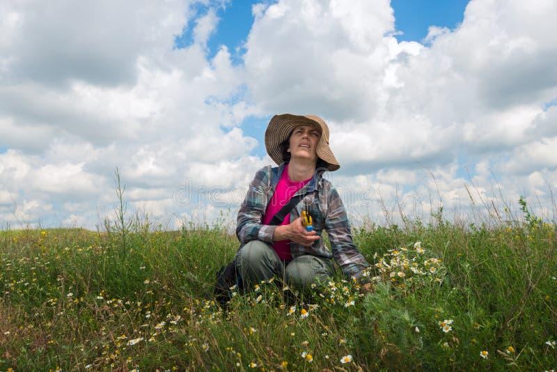 作妇女,帽子的,在豪华的绿草中坐 免版税图库摄影