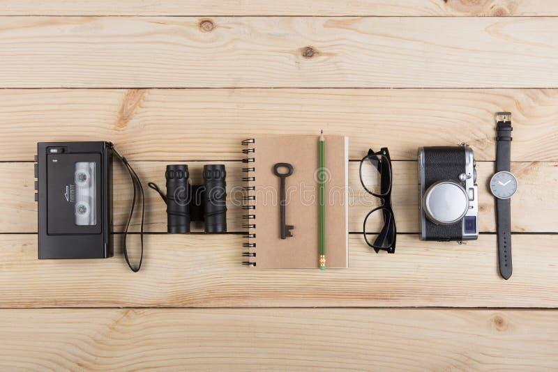作家、新闻工作者或者旅客书桌-在木背景的录音机、笔记薄和照片照相机 库存图片
