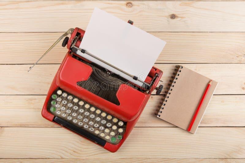作家或新闻工作者工作场所-在木书桌上的葡萄酒红色打字机 图库摄影
