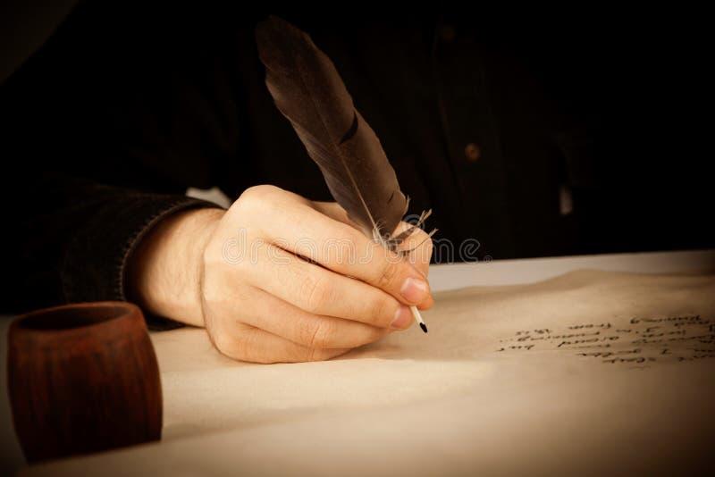 作家拿着在写信纸和书写p的钢笔 免版税库存照片