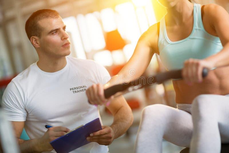 作指示的教练员健身房的一名妇女 免版税库存照片