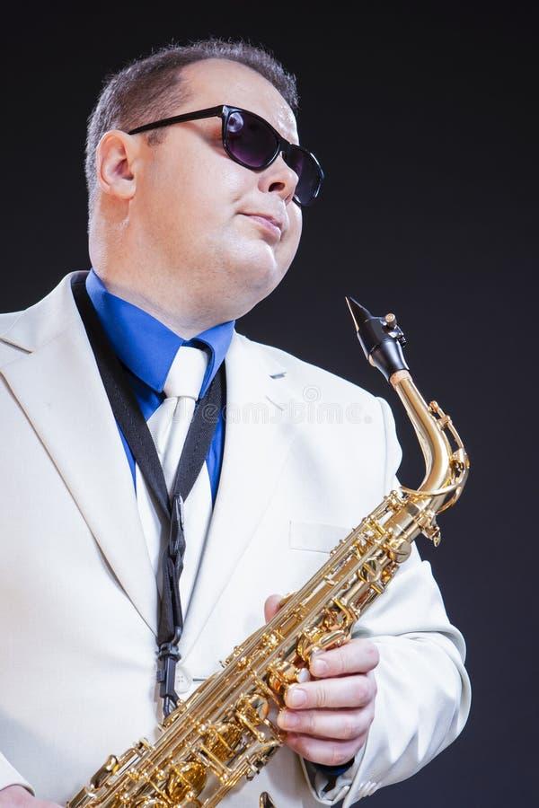 作摆在有萨克斯管的太阳镜的男性萨克斯管吹奏者 库存图片