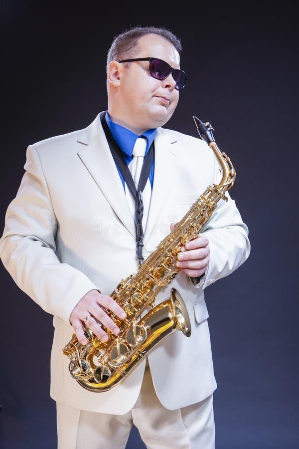 作摆在有萨克斯管的太阳镜的男性萨克斯管吹奏者 库存照片
