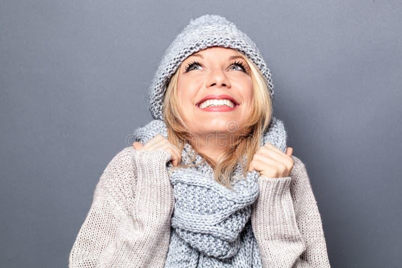 作有冬天帽子和想象力的年轻白肤金发的妇女 免版税库存图片