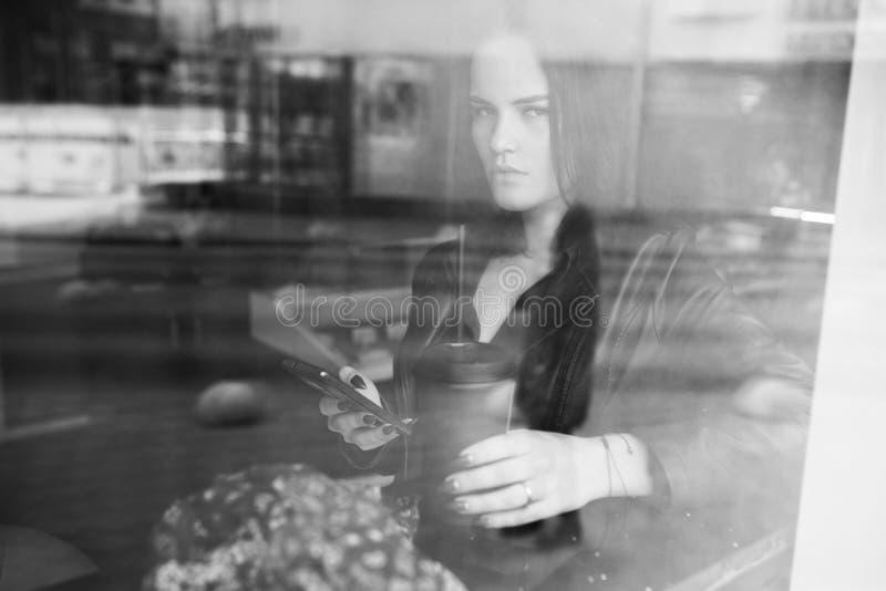 作梦关于某事和喝咖啡的一个逗人喜爱的少妇的射击,当看在咖啡馆时的窗口 免版税图库摄影