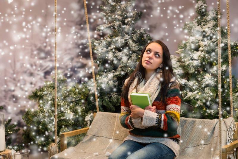 作梦可爱的女孩,当坐与毯子时的摇摆 免版税图库摄影