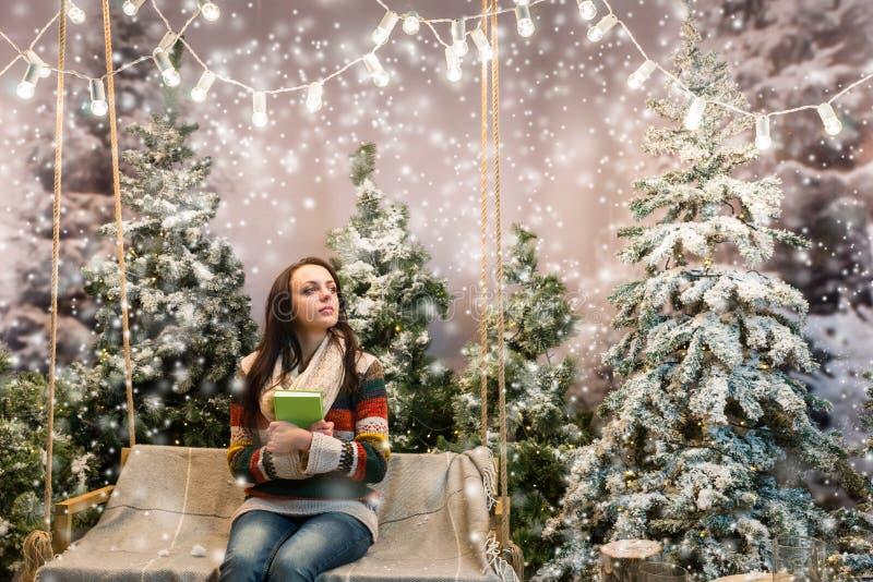 作梦逗人喜爱的女孩,当坐与下时毯子的摇摆 库存图片