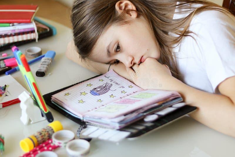 作白日梦与她的头的美丽的青春期前的女孩画象说谎在看她的浪漫日志的手上 免版税库存照片