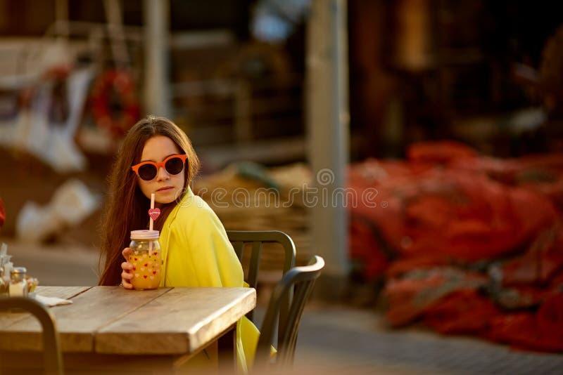作白日梦在咖啡休息 记住沉思愉快的妇女看坐直在酒吧,咖啡店的边喝橙色ju 库存照片