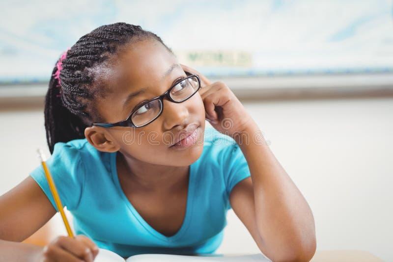 作白日梦在她的书桌的逗人喜爱的学生在教室 图库摄影
