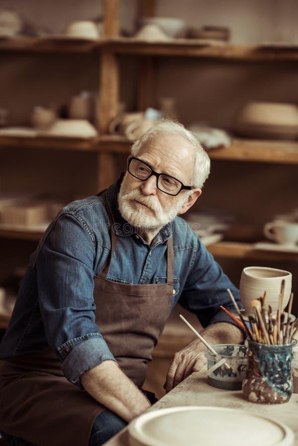 作白日梦的围裙的资深陶瓷工坐在桌上和 免版税图库摄影