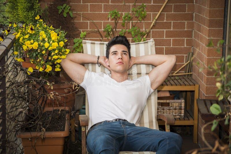 作白日梦英俊的年轻的人在阳台上 免版税库存照片