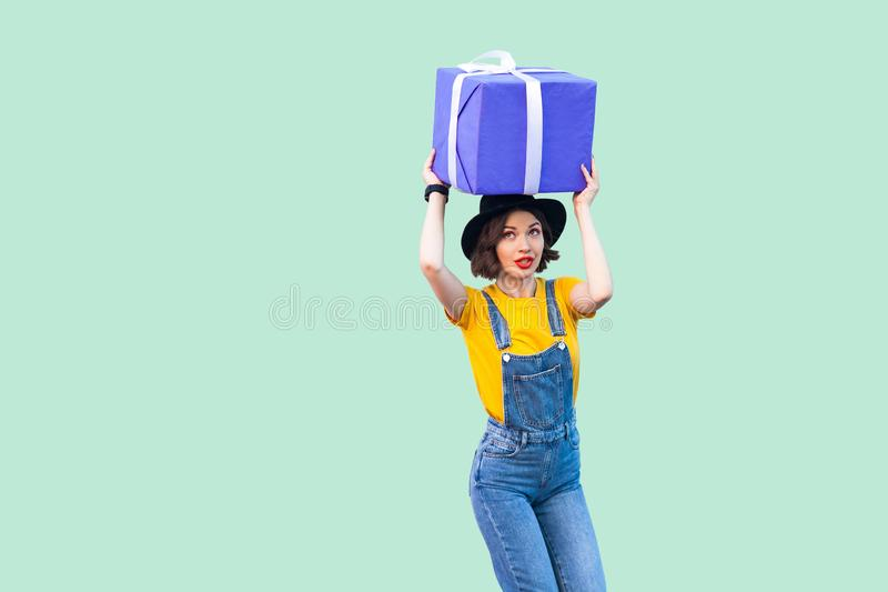 作行家穿戴的正面少女在牛仔布总体和黑帽会议身分和举行在头巨型大重的礼物下 免版税库存照片