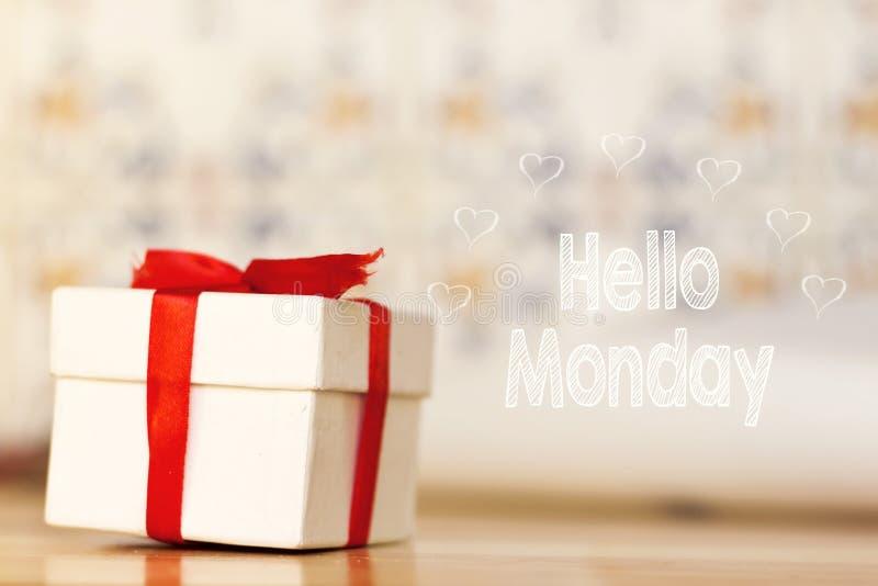 你好与白色礼物盒的星期一消息有在木背景的红色丝带的 图库摄影