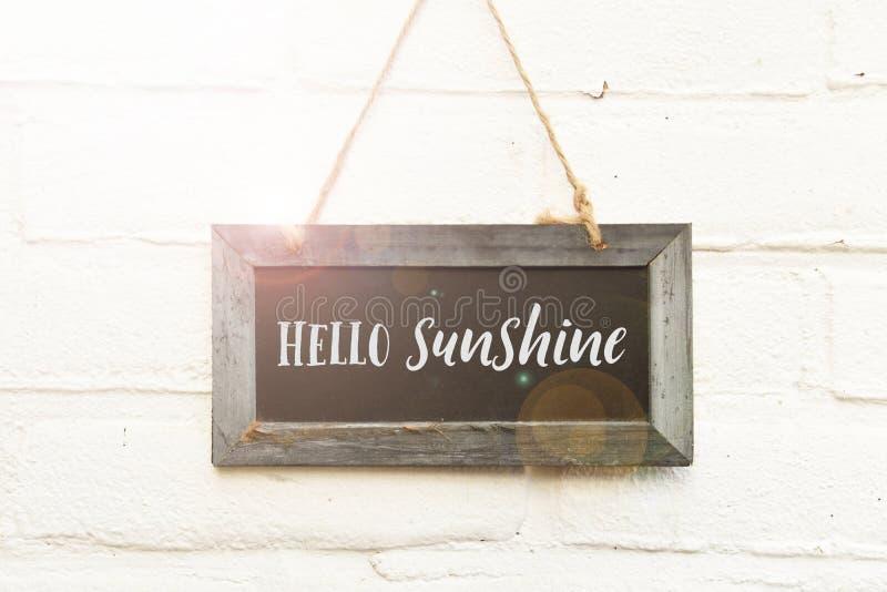 你好在垂悬在白色砖的黑板的阳光受欢迎的文本 免版税库存照片