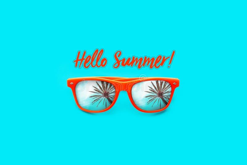 你好在大深蓝背景中有棕榈树反射的夏天文本橙色太阳镜隔绝的 免版税库存图片