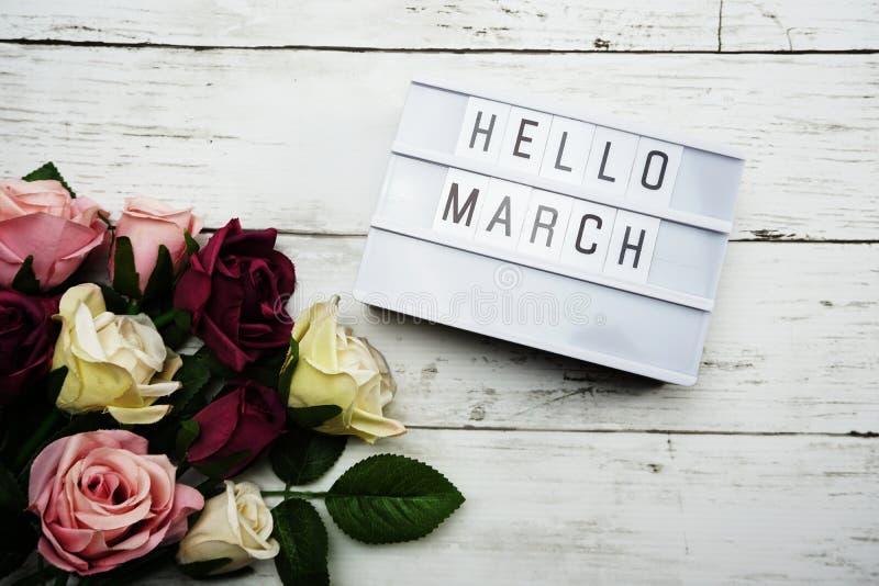 你好在灯箱的3月词有玫瑰的开花在木背景的花束 库存图片