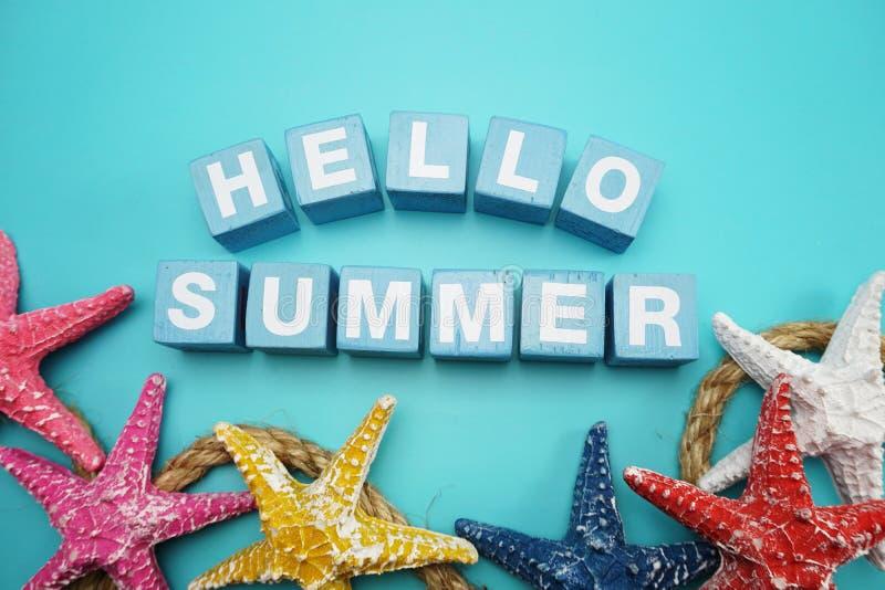 你好夏天字母表信件和五颜六色的海星装饰在蓝色背景 免版税库存照片