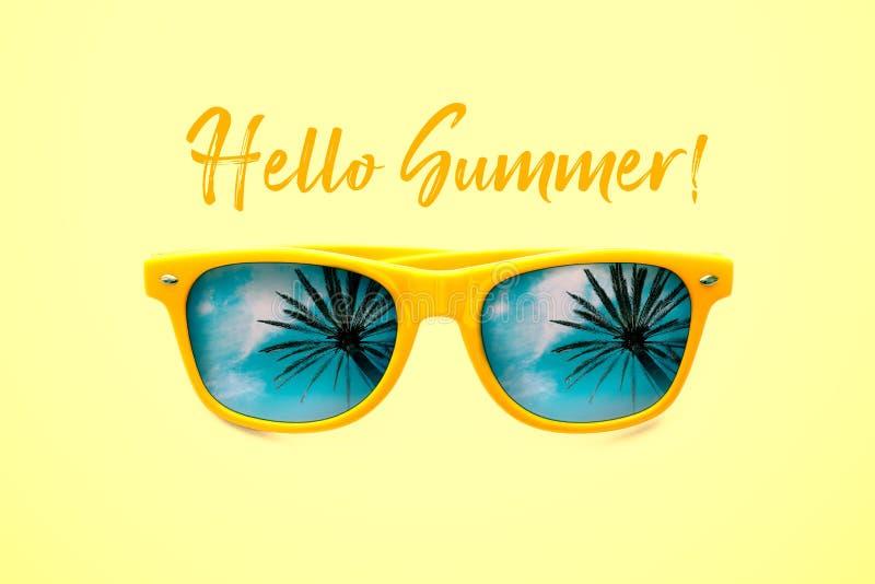 你好夏天概念图象:在淡色黄色背景中有棕榈树反射的黄色太阳镜隔绝的 免版税库存照片