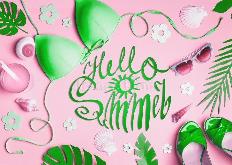 你好夏天 在桃红色背景,顶视图的女性海滩辅助部件 舱内甲板被放置的绿色比基尼泳装,太阳镜,与鸡尾酒的凉鞋, 免版税库存图片