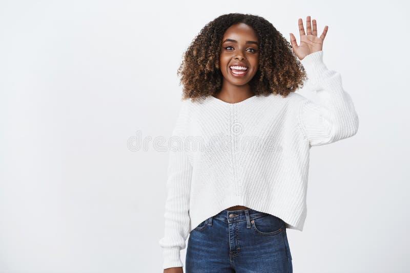 你好朋友怎么您 迷住友好的微笑的宜人的非裔美国人的妇女培养手挥动的问候的画象 免版税图库摄影