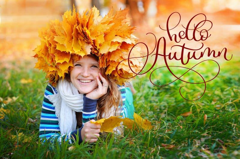 你好秋天书法在年轻美丽的女孩的字法文本在秋天公园 免版税库存图片